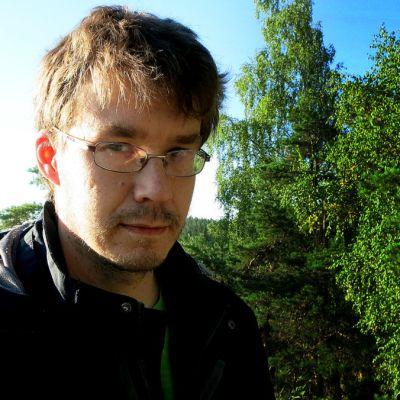 Silmälasipäinen mies seisoo Aulangon näköalapaikalla ja katsoo kameraan.