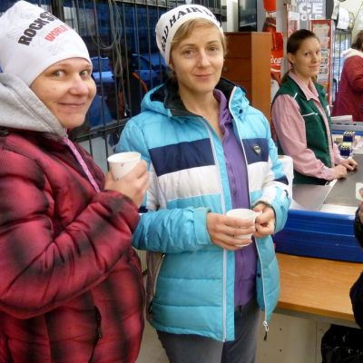Neljä naista juovat kaupassa kahvia pahvimukeista