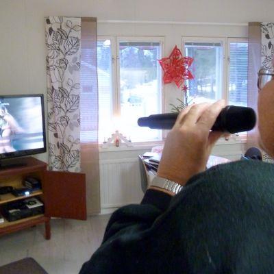 Juhani Tikka laulaa karaokea Meän talolla Torniossa.