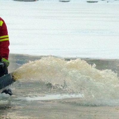 Työmies pumppaa vettä järven jäälle.