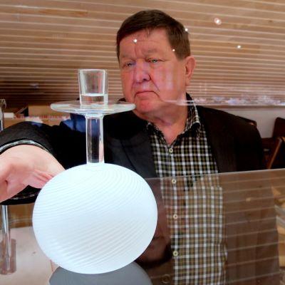 Mies tarttumassa lasivitriinissä olevaan esineseen.