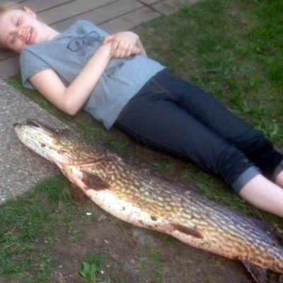 Tyttö makaa nurmikolla vieressä pitkä ja iso hauki