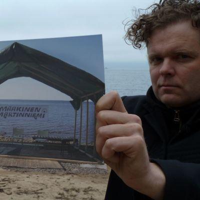 Jukka Takalo esittelee kuvaa Maakisen Martinniemen esiintymislavasta.