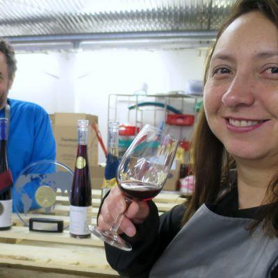Mies tuosuttelee viini lasissa ja nainen hymyilee etualalla lasi kädessään