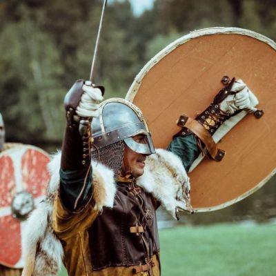Viikinkiasuihin pukeutunut mies hurraa kilpi ja miekka pystyssä