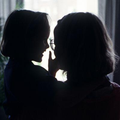 Äiti lapsi sylissään valoisaa ikkunaa vasten kuvattuna