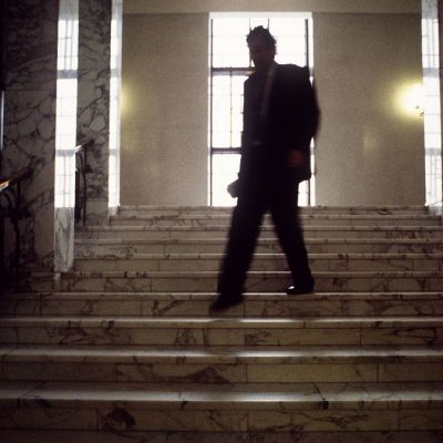 Tumma mieshahmo laskeutuu portaita pitkin eduskunnassa