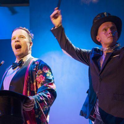 Kaksi miestä pukeutuneina taikurin vaatteisiin