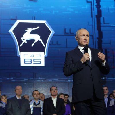 Putin puhuu lavalla mikrofoniin. Taustalla näkyy joukko tehtaan työntekijöitä ja GAZ-yhtiön logo.