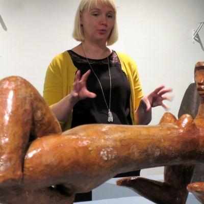 Keltaasuinen vaalea nainen katselee seläällään olevaa naishahmoa