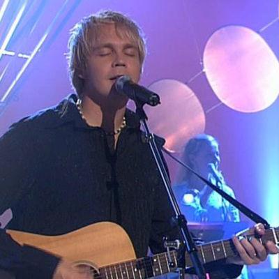 Juha Tapio laulaa ja soittaa kitaraa
