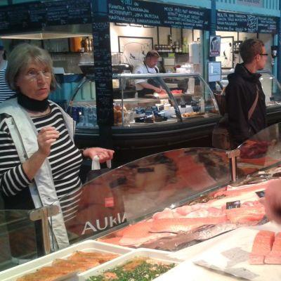 Myyjä fileoi kalaa, asiakas toisella puolen tiskiä.