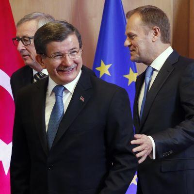 Juncker, Davutoğlu ja Tusk poseeraavat Turkin ja EU:n lippujen edessä.