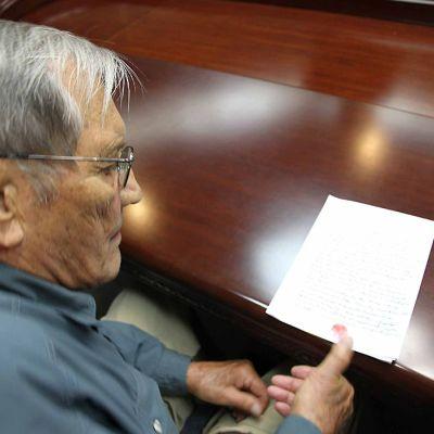 Merrill Newman painaa punaisen peukalonjälkensä paperiin, jossa hän pyytää anteeksi sodanaikaisia rikoksiaan.