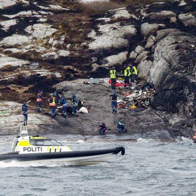 Joukko poliiseja ja pelastustyöntekijöitä tutkii rantakallioita. Saaren edustalla ajaa poliisin moottorivene. Oikeassa reunassa punainen kumivene ajaa kohti rantaa.
