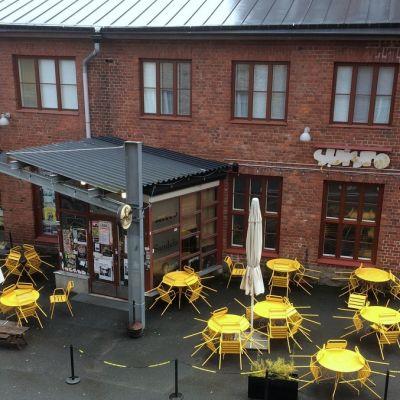 Kuva ulkoa Verkatehtaan sisäpihalta jossa on kirkkaan keltaisia terassipöytiä ja tuoleja