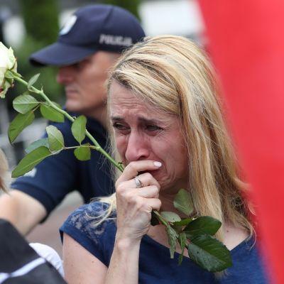 Valkoista ruusua pitelevä nainen, jolla on silmät kyynelissä. Taustalla poliisi.