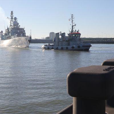 Hinaaja vetää harmaata sota-alusta satamaan. Auringon säteet heijastuvat laivan kyljestä. Etualalla näkyy satamalaituri.
