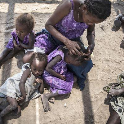 Kuvassa äiti istuu maassa kolmen lapsen kanssa. Äiti kampaa yhden lapsen hiuksia.