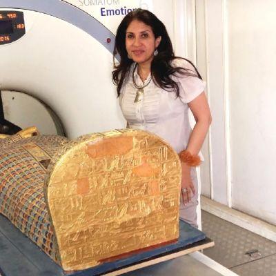 Faraon sarkofagi kerroskuvauslaitteen edessä. Vieressä seisoo valkoisiin pukeutunut nainen.