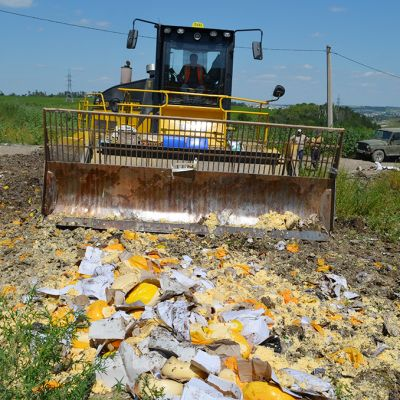 Kauhakuormaaja tuhoamassa juustoa ja muita elintarvikkeita