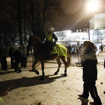 Ratsupoliisi ja kiakkovieraiden mielenosoittajia Tampere-talon edustalla.