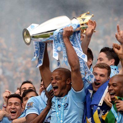 Manchester Cityn pelaajat juhlivat Valioliigan mestaruuspokaalin kanssa.