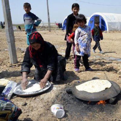Nainen paistaa leipää Hamam al-Alilin pakolaisleirillä Mosulissa huhtikuun alussa. Lapset seuraavat ympärillä.
