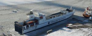 Ett fraktfartyg står i en hamn. Det är vinter.