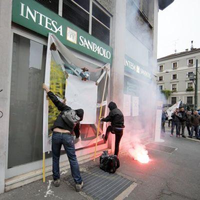 Mielenosoittajat töhrivät pankin julkisivua Milanossa 1. toukokuuta.