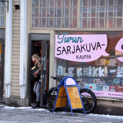 Asiakas kävelee ulos Turun Sarjakuvakaupasta.