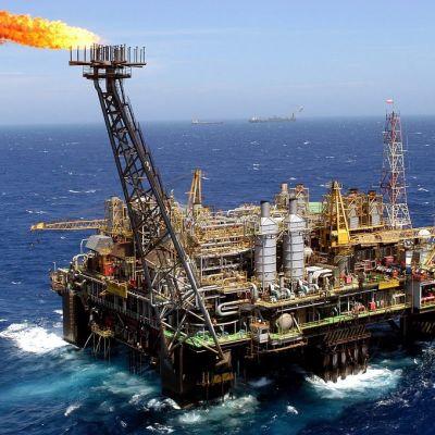 Brasilian Petrobras-yhtiön öljylautta merellä päivällä. Meri aaltoilee tummansinisenä, taivas on vaalea. Öljynporauslautan tornista nousee liekki, kun porauksen yhteydessä nousevaa kaasua poltetaan. Kaukana horisontissa näkyy kaksi alusta, mahdollisesti tankkereita.