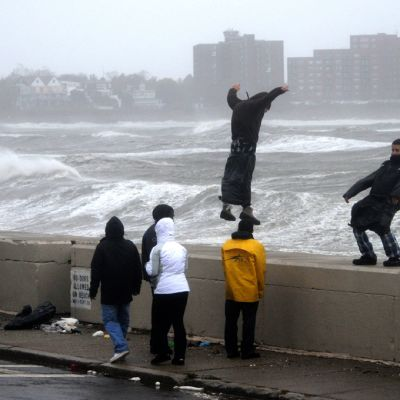Ihmisiä sillalla. Kaksi tasapainoilee kaiteella.