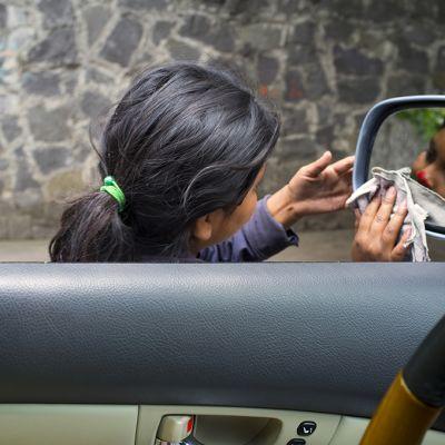 Tyttö pesee auton peiliä liikennevaloissa.