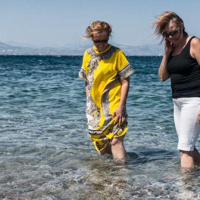 Naiset kahlaavat rantavedessä.