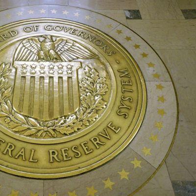 Yhdysvaltain keskuspankin Federal Reserven hallituksen keltainen vaakunakuvio lattiassa. Sinetin reunalla lukee versaaleilla: Board of Governors. The Federal Reserve System. Keskellä on kuva kotkasta, joka istuu Yhdysvaltain lipun koristaman vaakunakilven päällä.