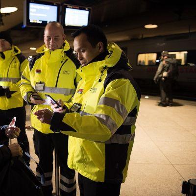 Kirkkaankeltaiseen vartijan asuun pukeutunut mies tarkistaa vaalean sinitakkisen naisen henkilöllisyystodistusta. Taustalla näkyy kaksi muuta samanlaisiin keltaisiin pusakoihin pukeutunutta miestä.