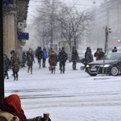 Nainen kerjäämässä kadulla lumisateessa.