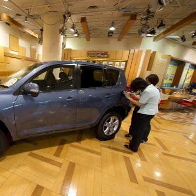 Kaksi miestä tutkii siniharmaata katumaasturia sisällä tilassa, jossa on parketti ja paneloidut seinät.