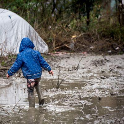 Poika kahlaa mudassa, taustalla kupoliteltta.