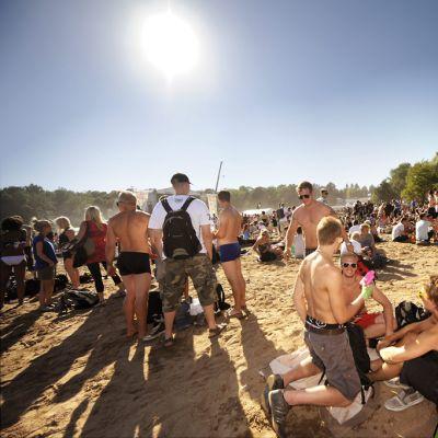 Festarivieraita aurinkoisella hiekkarannalla.