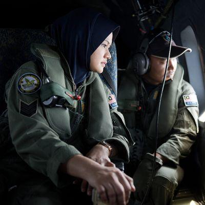 Malesian ilmavoimien henkilöstö tähystää mahdollisia Malaysia Airlinesin lentokoneen jäänteitä etsintälennolla Malakansalmen yllä.