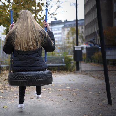 Tyttö keinumassa yksin