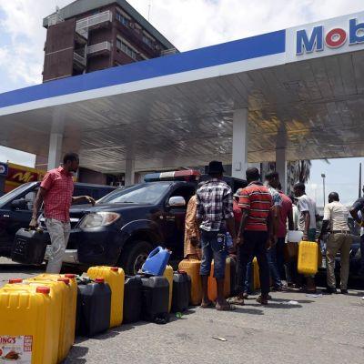 Ihmiset jonottavat polttoainetta bensiiniasemalla.