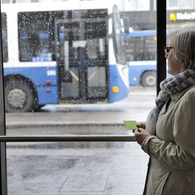 Työmatkalainen bussipysäkillä.