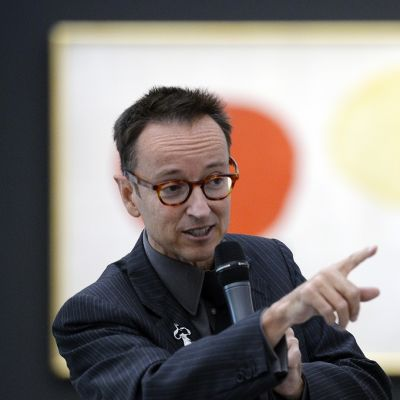 Miró osoittaa sormella yleisöön, taustalla taideteos, jossa punainen ja oranssi ympyrä.