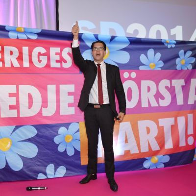 Jimmi Åkesson käsi ylhäällä lakanan edessä, jossa lukee Sveriges tredje största parti.