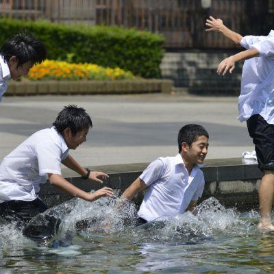 Koululaiset pakenivat hellettä puiston suihkulähteeseen Tokiossa 8. heinäkuuta.