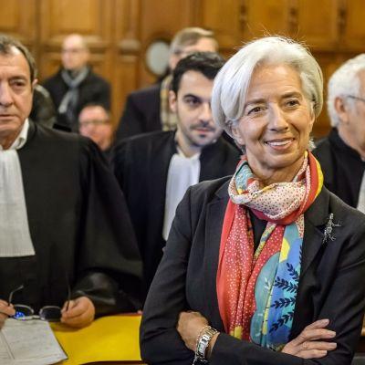 Lagarde seisoo oikeussalissa kädet puuskassa ja hymyilee. Hänellä on kaulassaan värikäs huivi. Taustalla näkyy oikeuden jäseniä.