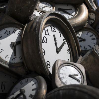 Pilariksi kasattuja pronssisia kellotauluja, kaikissa eri kellonaika.